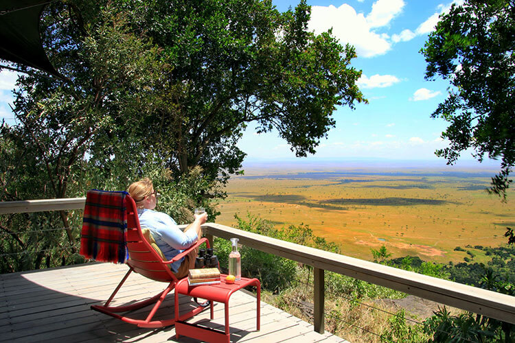 Jennifer sitting in a rocking chair with a G&T on our deck at Angama Mara