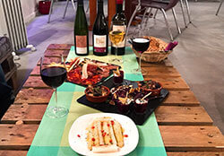 White asparagus with pomegranite, a charcuterie plate, and a plate with hummus, octopus salad, and couscous paired with three natural wines at Comptoir St. Vincent Natural Wine Bar