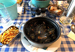 A pot of steaming mussels in curry sauce with a side of fries and wine at Les Moules du Cabanon
