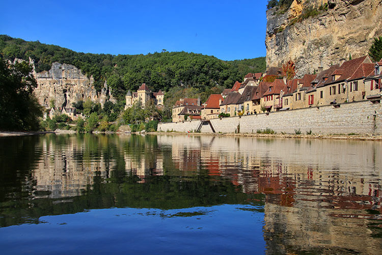 The village of La Roque-Gageac and Château de La Malartrie reflect on the Dordogne River