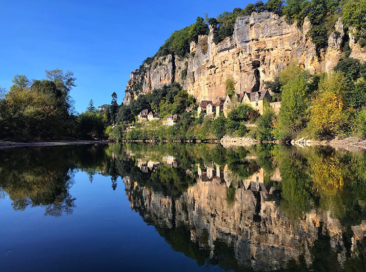 The village of Cénac-et-Saint-Julien and its limestone cliffs reflects on the mirror-like Dordogne River