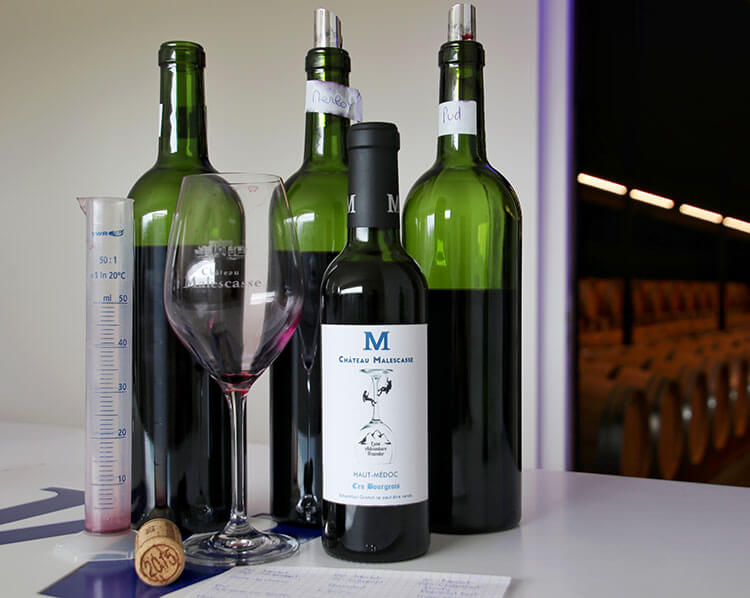 Bottles of Merlot, Cabernet Sauvignon and Petit Verdot for blending, graduated cylinder, and our finished bottle of wine at Château Malescasse
