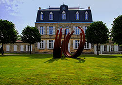 A metal sculpture sits on the lawn in front of the 19th century Château Malescasse