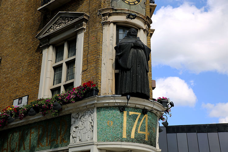 A fat, happy monk stands over the corner of the Blackfriar Pub
