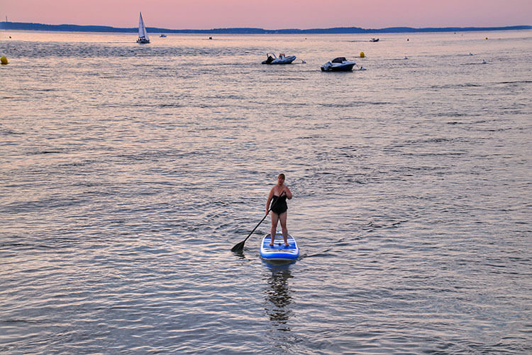 Jennifer paddle boarding in the soft pink light after sunset at the Bassin d'Arcachon