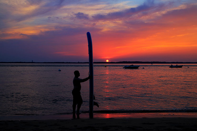 Tim holding the iSUP board vertical at sunset at Arcachon