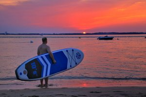 Tim carrying the SUP board while looking at the sunset at the Bassin d'Arcachon