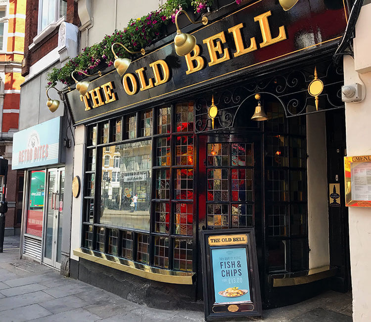 The exterior of The Old Bell Tavern with its stained glass window