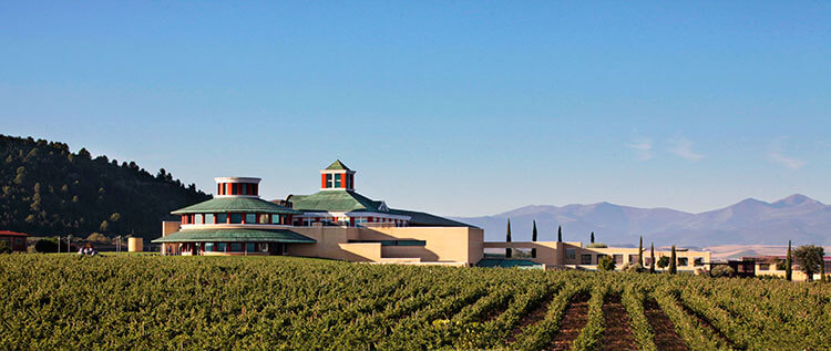 The modern and minimalistic Vivanco winery surrounded by vineyards with the mountains in the distance in La Rioja, Spain