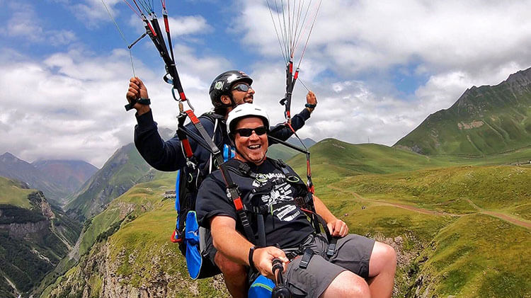 Tim is all smiles on his tandem paraglide in Kazbegi, Georgia
