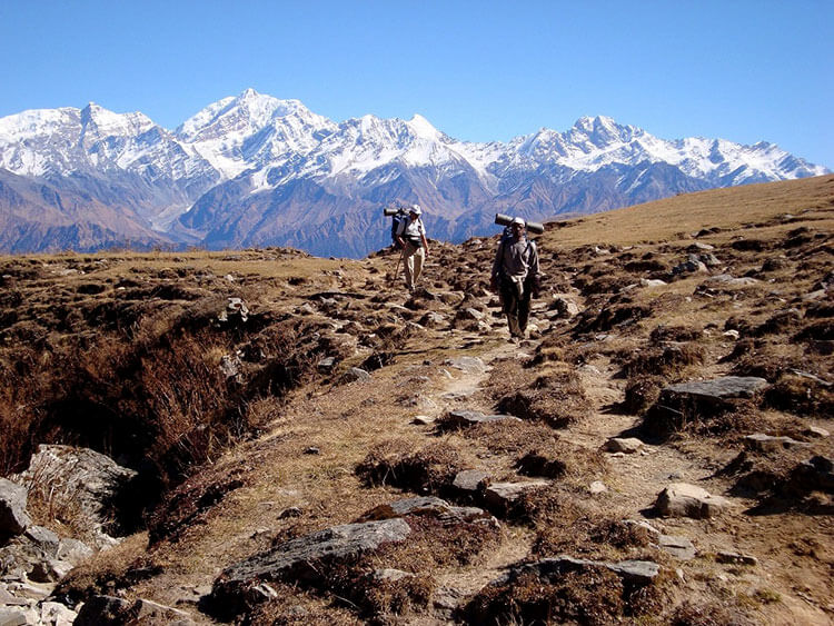 Two trekkers walk on a flat part of the trail on a clear day with the Himalayas visible behind them