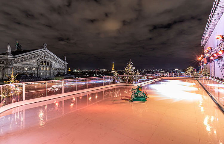 The rooftop rink at Galeries Lafayette with a view of the Eiffel Tower at nighttime in Paris