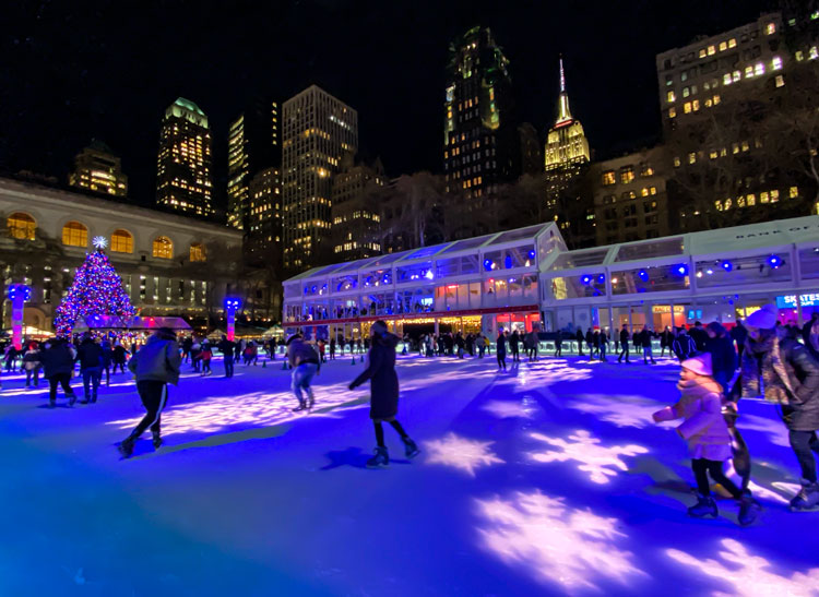 White snowflakes are projected on the ice rink at Bryant Park as ice skaters skate around the rink after dark