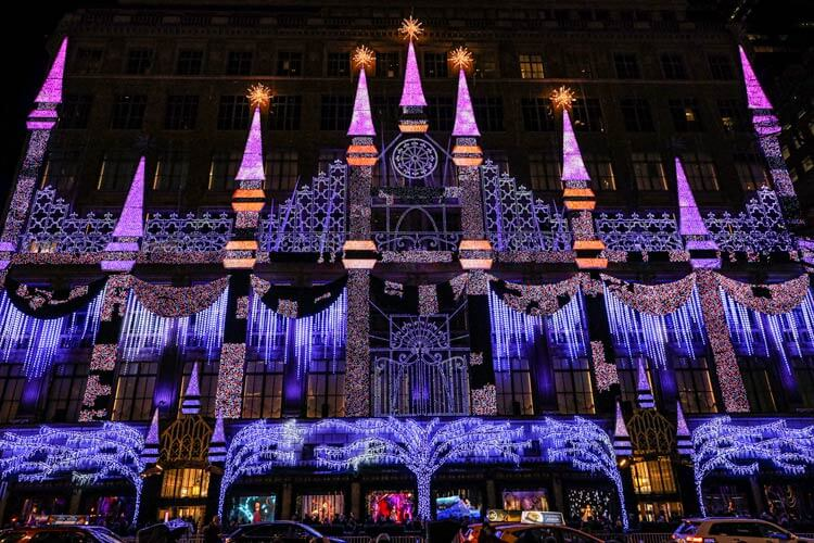 The castle affixed to the facade of Saks Fifth Avenue light up in pinks and purples during the light show