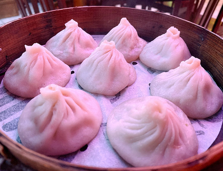 A bamboo steamer basket filled with eight pork soup dumplings at Shanghai Dumpling in NYC's China Town
