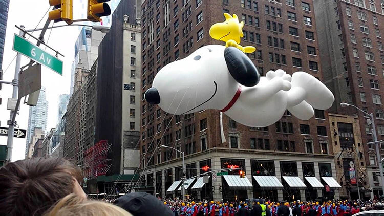 The Snoopy balloon passes by The Wayfarer during the Macy's Thanksgiving Day Parade in NYC