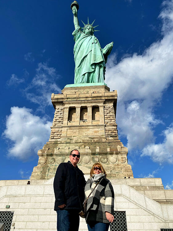 Jennifer and Tim pose for a photo in front of the pedestal of the Statue of Liberty