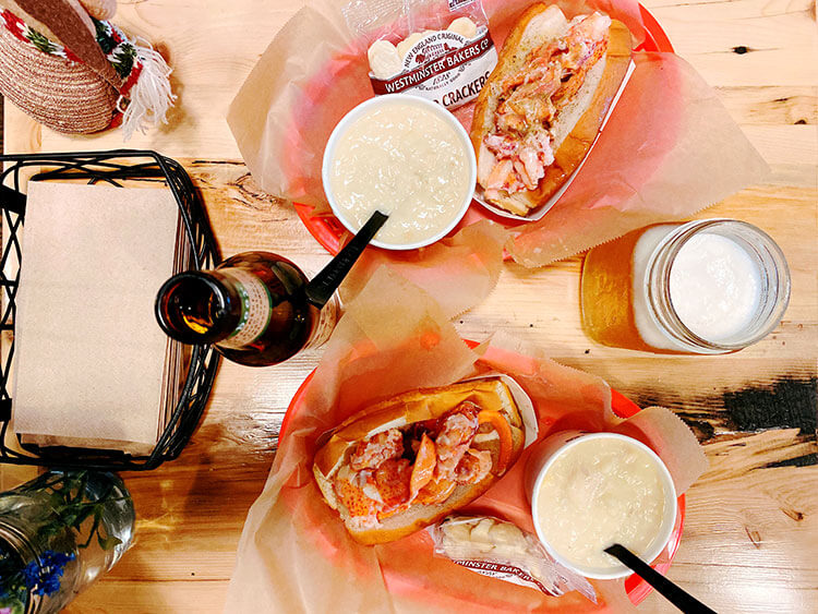 Lobster roll in a basket with a side cup of clam chowder at Luke's Lobster in NYC