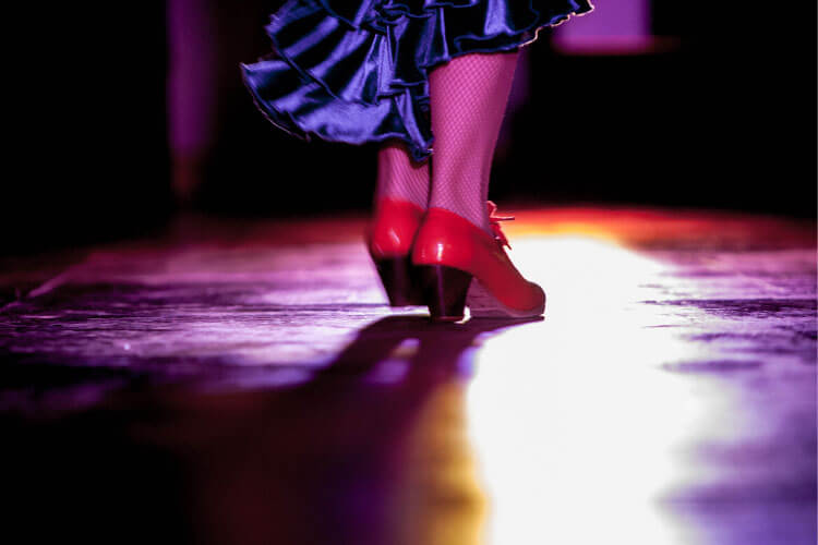 A close up of a flamenco dancer's red shoes