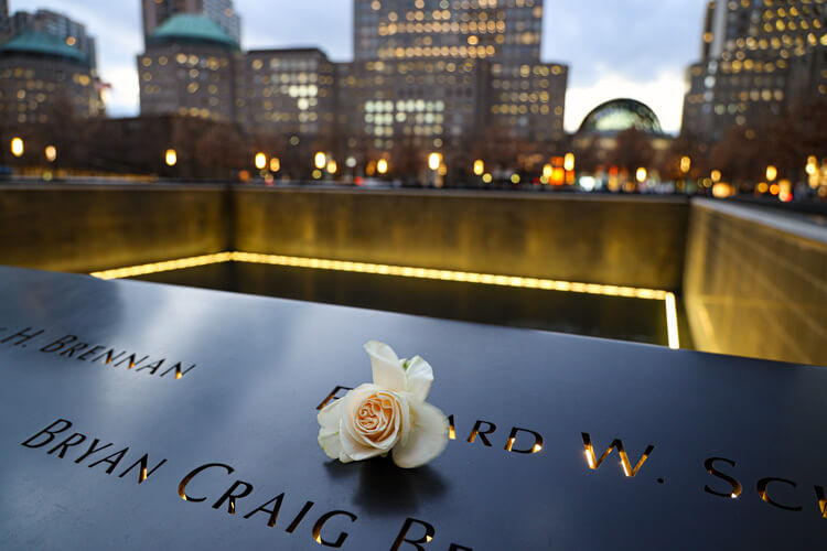 A white roses sits atop some names at the 9/11 Memorial in NYC