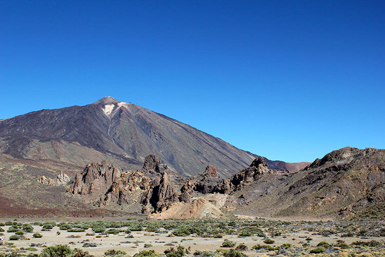A view of Mount Teide with its snowy cone and the Roques de García rock formations standing in front as seen from a distance
