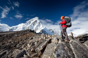A woman stops to admire a snowy Nepal peak on a climbing expedition