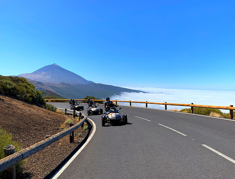 The group from the Can Am Spyder tour on a curve of the road with Mount Teide high above in the background in Tenerife