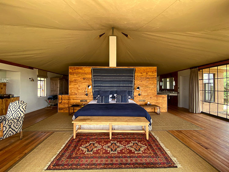 Inside the tent with king size bed, simple decor and a sitting area at Loisaba Lodo Springs
