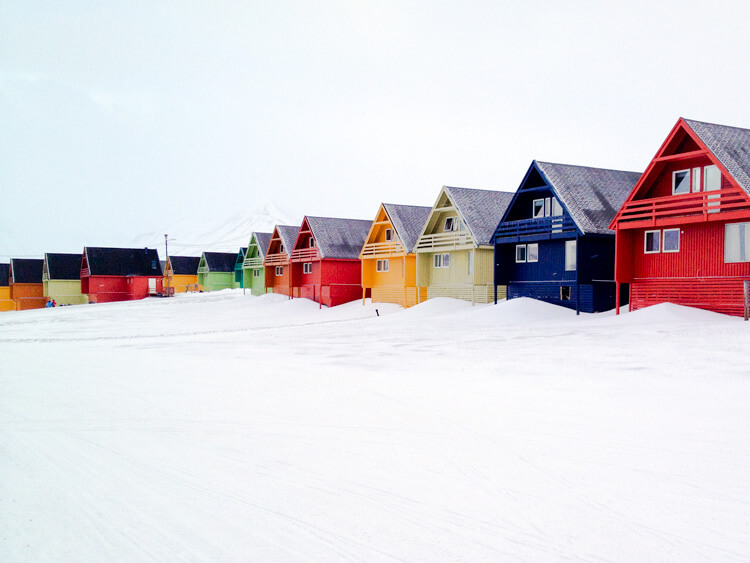 A row of houses painted in various colors and built on stilts in Longyearbyen, Svalbard