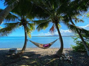 Jennifer relaxes in a hammock strung between two palm trees with the blue sea behind her on Ilet Oscar in Martinique
