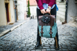 A woman holds a compact camera along with a backpack while standing on a cobbled street