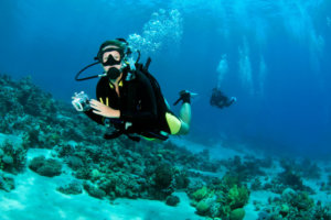 A diver carries a camera in an underwater housing while diving along a coral reef