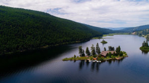 An aerial of the Island Lodge located on a small island in the middle of a lake at Paws Up Resort Montana