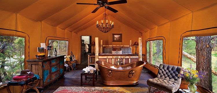 The luxury glamping tent at Cliffside Camp at Paws Up Resort Montana with a four poster bed and brass metal bath