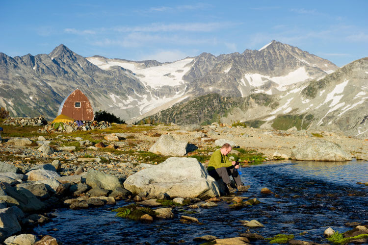 A hiker uses a travel water filter in a mountain lake