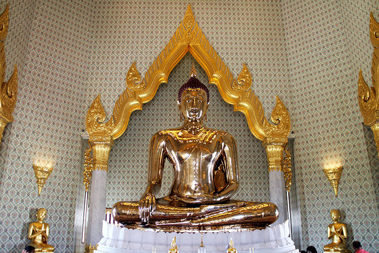 The seated solid gold Buddha sits on a pedestal in Wat Traimit in Bangkok's Chinatown