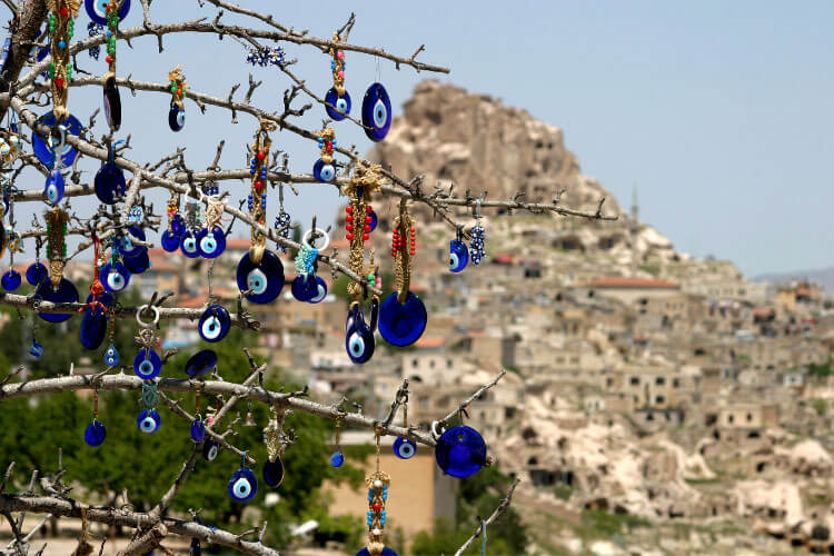 Turkish eye beads hand on a tree at a viewpoint looking out to the fairy chimneys of Cappadocia, Turkey