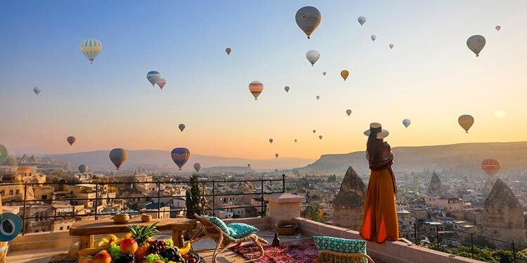 A woman stands on the sun terrace at sunrise watching hot air balloons fill the sky from Mithra Cave Hotel in Cappadocia