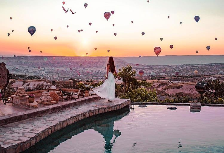 A woman stands at the edge of the pool at Museum Hotel in Uchisar watching sunrise and hundreds of hot air balloons in Cappadocia