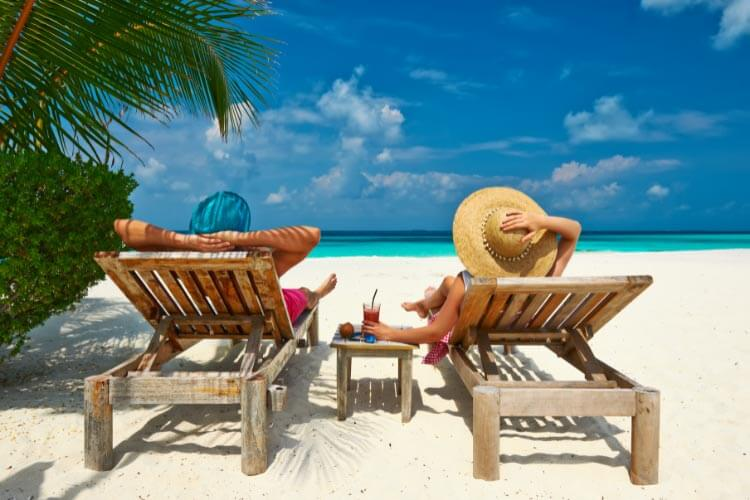 A couple lounges on beach chairs on a white sand beach in the Maldives