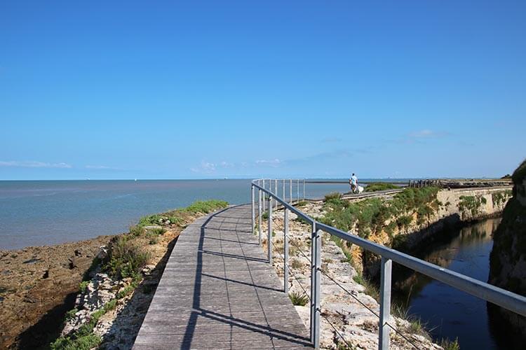 A coastal path leads around the island toward the Île d'Aix lighthouse